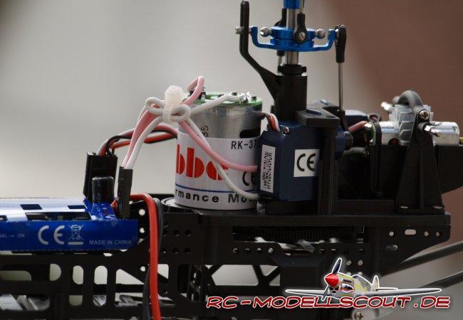 """Zwei Mini-Servos dienen zur Anlenkung der Taumelscheibe und übertragen Steuerbefehle für Roll und Nick auf den Rotorkopf. Auf ein drittes Servo kann verzichtet werden, da der Hubschrauber seinen Auftrieb über die Drehzahl des Hauptrotors erhält und somit kein Pitch zum Einsatz kommt. Schwarzer Kunststoff dominiert das Chassis des robbe ARROW PLUS. Die gesamte """"Intelligenz"""" des Hubschraubers versteckt sich in zwei kleinen Platinen, sauber verpackt mittels einer blauen Hülle aus Kunststoff. Die Elektronik beinhaltet sowohl 2,4 GHz-Empfänger, Regler als auch den 3-Achsen-Gyro, der Flybarless erst möglich macht. Durch das zentrale Bauteil macht das Chassis einen sehr aufgeräumten Eindruck und die Anzahl der Verkabelungen ist überschaubar."""